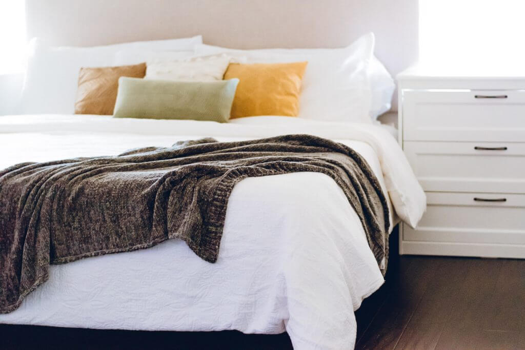 Overview of pillows on a bed with a grey throw