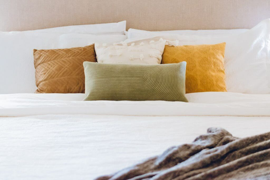 Pillows on a bed with a grey blanket