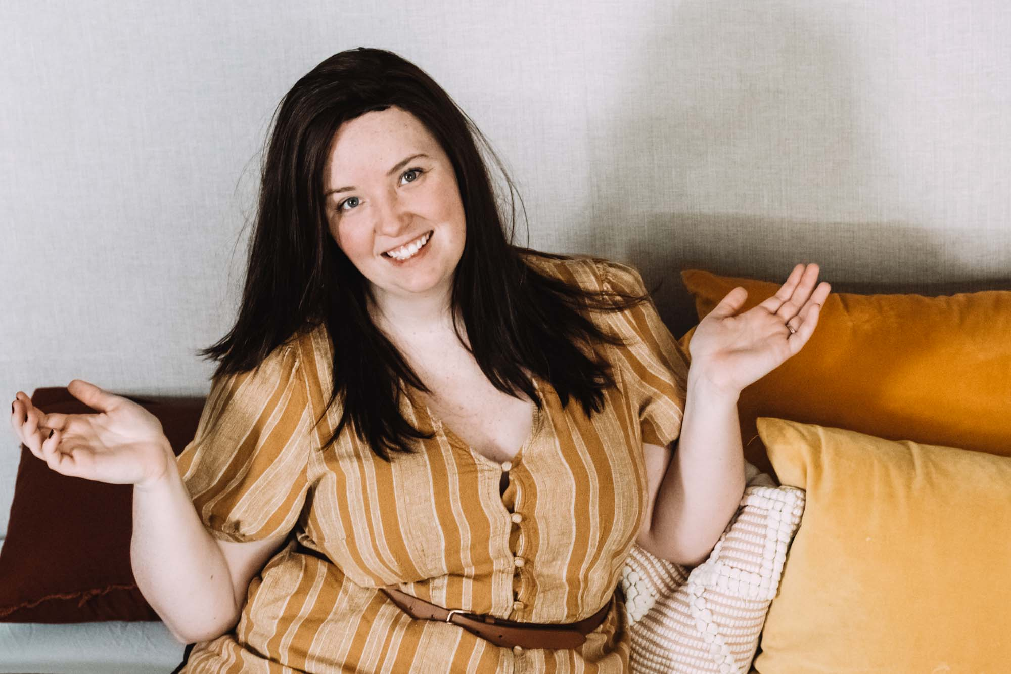 Catherine Ballard sitting on a bed with gold pillows for the Adjustable Split King Mattress Annoyances post.